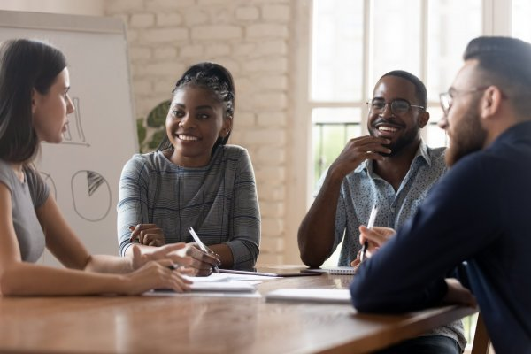 Multi racial employees gathered together at modern boardroom listening european female ceo at group meeting, company representative and client negotiations or teamwork corporate seminar study concept